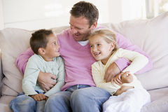 Man and two children sitting in living room stock photography