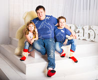 Man and two children sitting in living room smiling Royalty Free Stock Photography