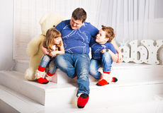 Man and two children sitting in living room smiling Stock Image