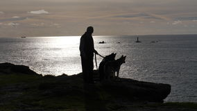 Man with two dogs silhouetted on the cliffs in the evening light in Cornwall UK Royalty Free Stock Photography