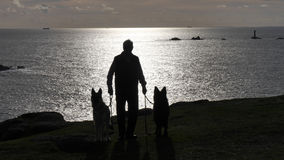 Man with two dogs silhouetted on the cliffs in the evening light in Cornwall UK Stock Images