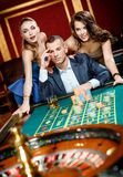 Man with two girls playing roulette at the gambling house Stock Photography