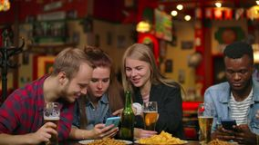 A man and two girls are sitting in a bar and looking at the phone screen while in the company of friends stock video