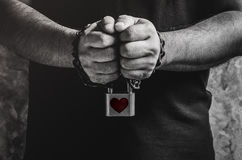 A man of two hands chained with old rusty chain and red heart sh. Ape over padlock on concrete wall Royalty Free Stock Photo