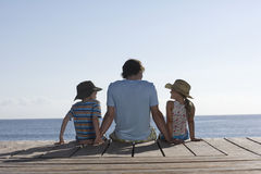 Man With Two Kids Sitting On Jetty. Rear view of a man with two children sitting on jetty stock photos