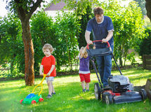 Man and two little sibling boys having fun with lawn mower Royalty Free Stock Photo