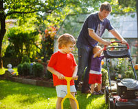 Man and two little sibling boys having fun with lawn mower Royalty Free Stock Image