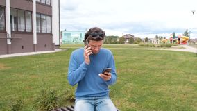 Man with two mobile phones sitting on the bench near the home. Calling and typing a message. Man with two mobile phones on the bench near the home stock footage