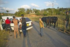 Man with two oxen pulling sled past broken down Fiat car in the Valle de Vi�ales, in central Cuba Royalty Free Stock Photos