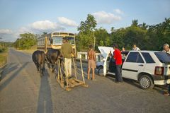 Man with two oxen pulling sled past broken down Fiat car in the Valle de Vi�ales, in central Cuba Stock Photography