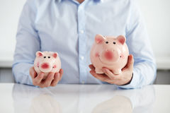 Man with two piggy banks. Man holding piggy banks over the table Stock Images