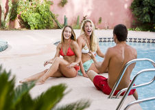 Man with two pretty girls by pool Royalty Free Stock Photography
