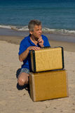 Man with two suitcases on beach Royalty Free Stock Photography