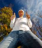 Man with two thumbs up. Bottom-up view of a guy showing thumbs up (blue sky background Royalty Free Stock Image