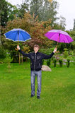 Man with two umbrellas Royalty Free Stock Image