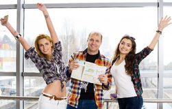 Man and two woman holding a passport with tickets and a map and look at the camera. Happy.Gathered in a guided tour Royalty Free Stock Image
