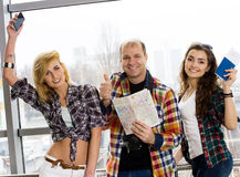 Man and two woman holding a passport with tickets and a map. Watch the camera and shows thumb up. Smile. Happy. Stock Images