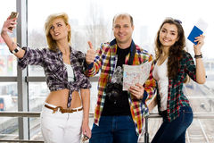Man and two woman holding a passport with tickets and a map. Watch the camera and shows thumb up. Smile. Happy. Royalty Free Stock Photo