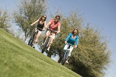 Man with two women cycling in park Royalty Free Stock Photo