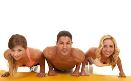 Man and two women front view push ups Stock Photography