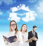 Man and two women getting education. Man and two women are standing with a book, a notebook and a clipboard under a cloud with a graduation hat in it. Concept of stock images