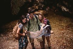 Friends using a map to find the route while hiking stock photos