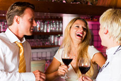 Man and two women in hotel bar. Man and two women in a hotel bar in the evening having glasses of red wine and probably a little flirt royalty free stock image