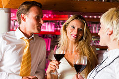 Man and two women in hotel bar. Man and two women in a hotel bar in the evening having glasses of red wine and probably a little flirt royalty free stock images