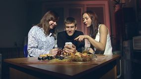 Man and two women looking at smartphone. The young man and two young girls sitting in the kitchen in the evening and look at smartphone stock video footage