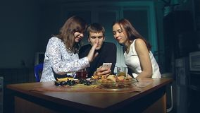 Man and two women looking at smartphone. The young man and two young girls sitting in the kitchen in the evening and look at smartphone stock video