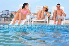 Man and two women reclining on chaise lounges Royalty Free Stock Images