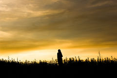 Man and two women stood watching the sunset.  Stock Image