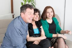 Man and two women watching television and enjoy. Man and two women are watching television on sofa and enjoy royalty free stock image
