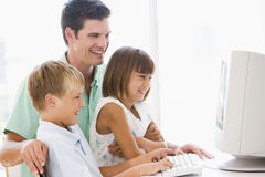 Man and two young children with computer Stock Photo
