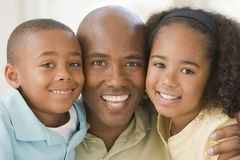 Man and two young children embracing and smiling stock image