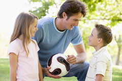 Man and two young children holding volleyball Stock Image