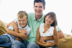 Man and two young children in living room smiling. At camera Royalty Free Stock Photo