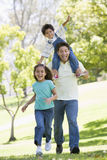 Man with two young children running smiling stock images