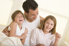 Man with two young children sitting in bed smiling Stock Photos
