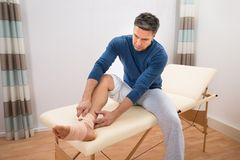 Man tying bandage to his foot Royalty Free Stock Images