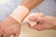 Man tying bandage to his wrist Stock Images