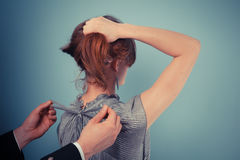 MAn tying bow on woman's dress Stock Images