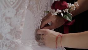 Man tying a corset on the bride`s wedding dress.  stock video