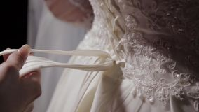 Man tying a corset on the bride`s wedding dress.  stock footage