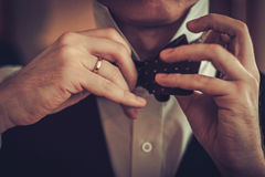 Man tying custom made bowtie.  stock photography