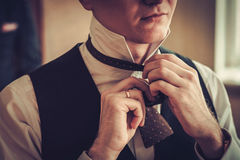 Man tying custom made bowtie.  royalty free stock photo