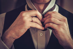 Man tying custom made bowtie.  stock images