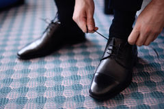 Man tying his black leather shoes. Selective focus Stock Image