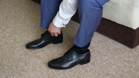 Man is tying his black shoes. Close-up stock video