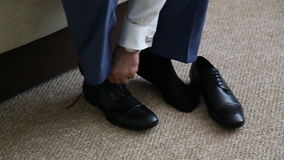 Man is tying his black shoes. Close-up stock video footage